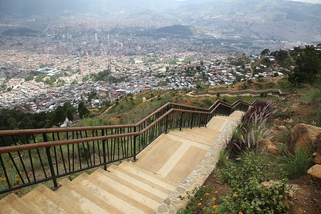 """A signature initiative of Medellin's current mayor, Anibal Gaviria, is the 56 km (35 mile) green belt.<br /> <br /> It will act both as a buffer to contain further slum sprawl and a forested park through which residents can stroll and cycle.<br /> <br /> Along with the jobs the project is providing, resident says they feel a sense of belonging and pride as they contribute to the transformation of their own neighbourhoods and improve their quality of life.<br /> <br /> They also say the network of paved paths and steps, drainage canals, vegetable allotments and cycle routes already built as part of the green belt have helped break down the """"invisible borders"""" that divide gang territory. <br /> <br /> By the end of this year, the green belt aims to employ nearly 5,400 people, the majority of them slum dwellers, including former gang members and single mothers.<br /> <br /> Medellin hopes the pathways with their stunning panoramic views will become a major tourist attraction.<br /> <br /> But as long as the whiff of marijuana remains in the air and gang members loiter on corners, it's going to take some time for all of Medellin's inhabitants to feel safe enough to venture up to the green belt."""