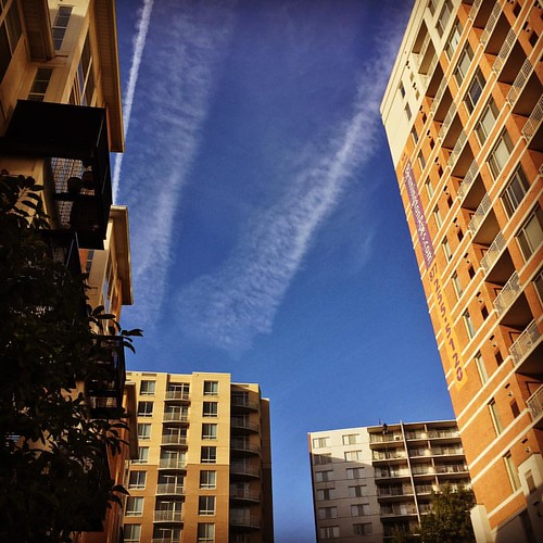 I like how the buildings frame the sky this morning (clouds, contrails).
