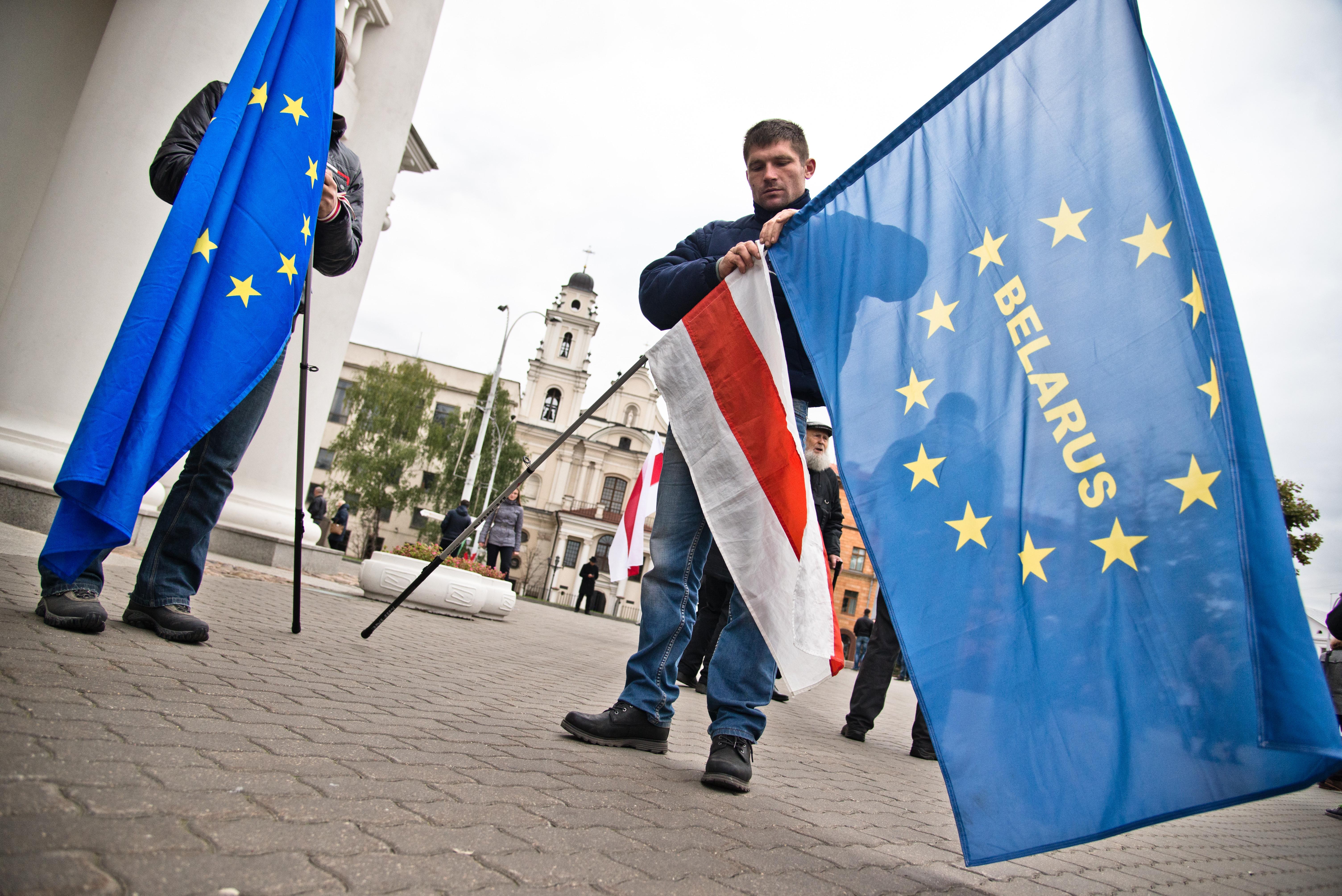 Menschen bei einer Demonstration mit belarussischer Oppositionsflagge und EU-Flagge