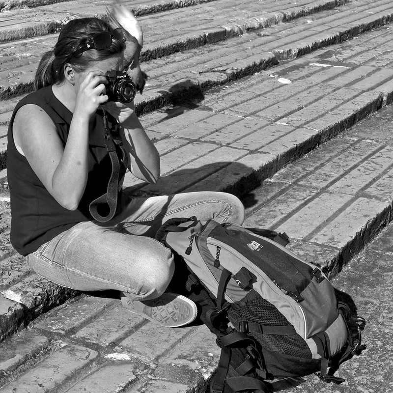 A photographer alternating between an analogique  and digital equipment