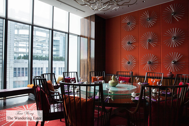 Private dining room wiht orange-red color theme; notice the hanging spiral artworks are made with ladles