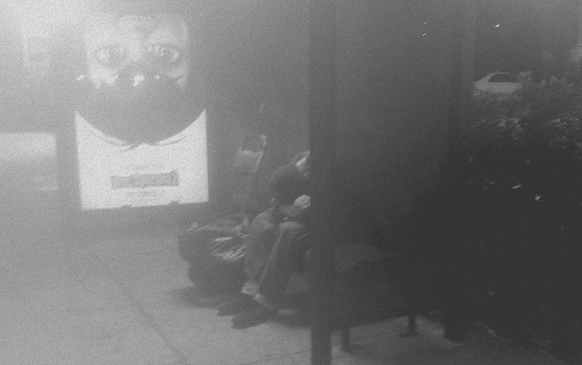 Homeless man in his 50th sleeping at a bus stop