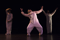 En la imagen se puede ver a tres componentes del grupo de teatro de pie sobre el escenario.  Fotografía cedida por Óscar Blanco Gutiérrez.