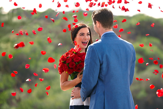 man and woman couple with raining red rose petals and red rose floral bouquet