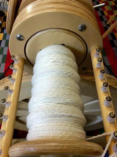Spinolution Mach 2 spinning wheel bobbin with 2-ply undyed Polwarth wool spun by irieknit