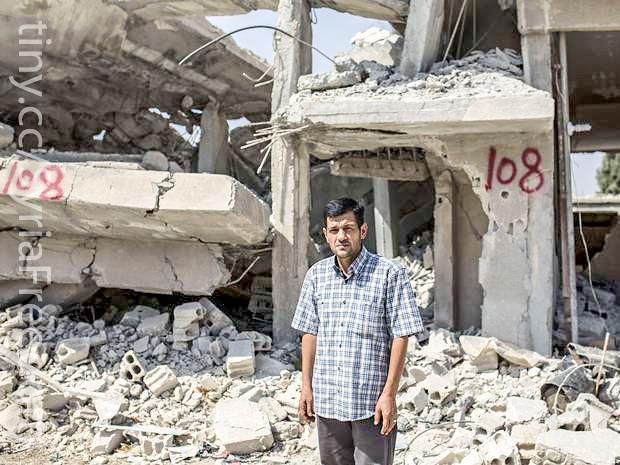 Abdullah Kurdi standing by his destroyed