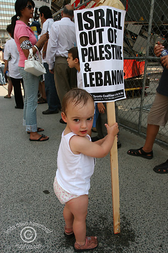Palestinian Baby Plays with Protest Sign