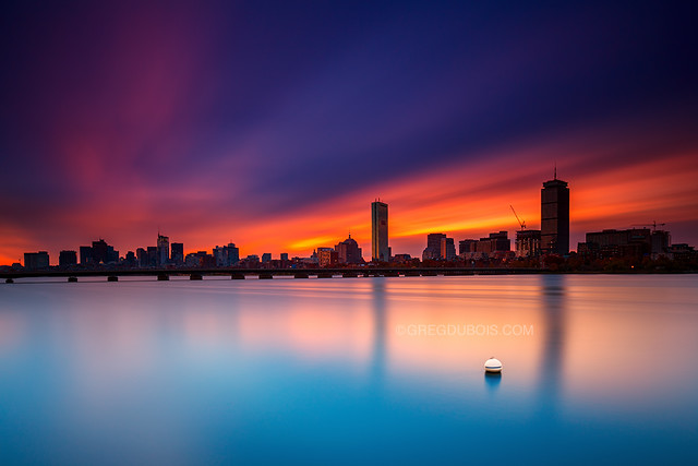Back Bay Boston Skyline with Prudential and Hancock Towers over Harvard Bridge and Charles River with Buoy at Sunrise from Cambridge MA USA