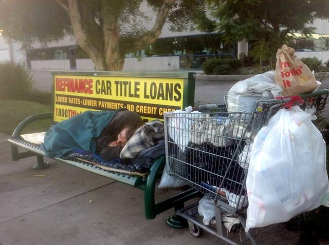 Homeless man sleeping on a street bench at sunrise