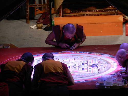 Tibetan Buddhist artist monks completing the lettering around the Kalachakra mandala, one fills in the white edge, others wear masks, plastic cups of colored sand, on stage, Kalachakra for World Peace, Washington D.C., USA | by Wonderlane
