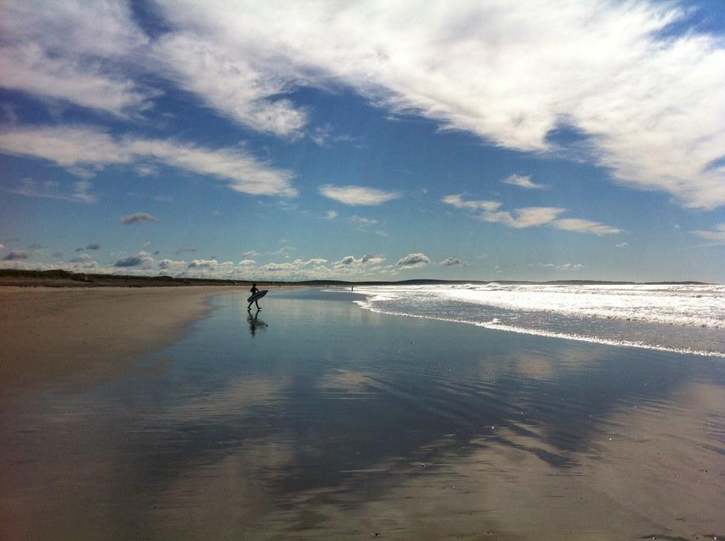 Surfer at Martinique Beach, Nova Scotia | A surfer heads out