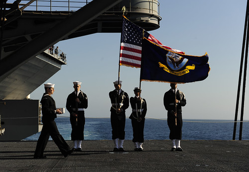 An urn bearer walks past the color guard aboard USS John C. Stennis during a burial at sea | by Official U.S. Navy Imagery