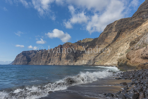 mountain hill slope cliff sky clouds horizon rock island sun sunrise blue sea ocean water sand beach black wave surf surge tide foam coast coastline landscape perspective ascent descent shadow mountainrange mountainpeak nature travel tourism spain canaryislands tenerife