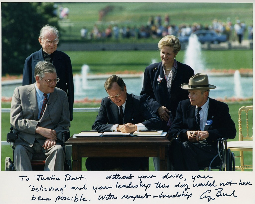 Photo of President George H. W. Bush signing the Americans with Disabilities Act inscribed to Justin Dart, Jr., 1990.