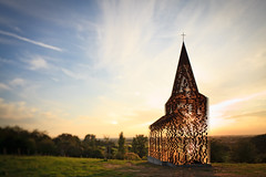 The Belgian architects duo Gijs Van Vaerenbergh (BE) built a see-through church for Borgloon. Reading Between the Lines is 10 metres high and consists of 100 stacked layers of steel plate in the shape of a church of Loon. The construction weighs a whopping 30 tons. The special way of construction makes the landscape always visible throughout the church, from far away and up-close. The church is therefore present but also absent in the landscape.  Practical info  On display: . permanent  Location: . walking path between the Sint-Truidersteenweg and the Roman Road (Romeinse Kassei)  Access: . Reading between the Lines is only accessible by foot or by bicycle. If you come by car, please park on the (Pb) parking at Sint-Truidersteenweg between Grootloonstraat and Neremstraat and continue by foot. From the parking you may follow the orange, blue, yellow or green walking route.  This art work is located in an agricultural area. Please respect the activities of the agricultural workers.  www.z33.be/en/z-out/pit/gijs-van-vaerenbergh-reading-betw...  part of pit - art in the public space of Borgloon-Heers | Z33 - art in public space  photos: Kristof Vrancken / Z33