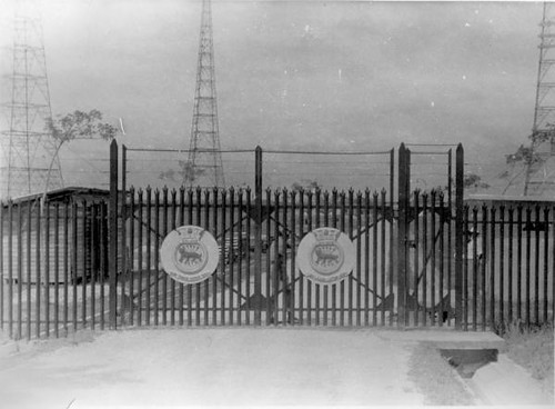 Kranji W/T 1937 - Main gates. The badge shows GYL-GYS [where normally the ships name is placed] and is of a tiger with electrical emissions [transmissions] above and below its body. The wording underneath [the motto ?] is in Malayan on the left gate and i