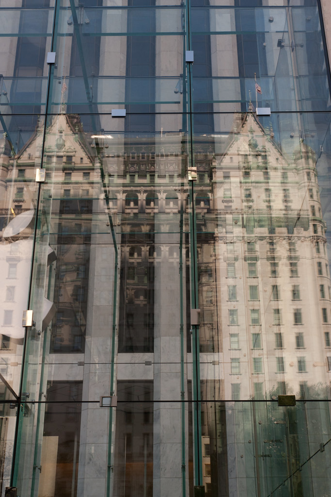 Plaza hotel reflected in the Apple store glass entrance.