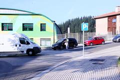 Un agente en labores informativas, junto a la hilera de vehículos que trasladan escolares