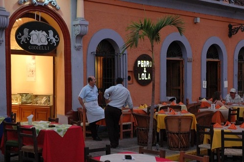 Two business men chatting, Pia Gioielli jewelers lion sign, a waiter from Pedro & Lola restaurant, set tables, palm tree, customers, Machado Square, Centro Historico, Sinaloa, Mexico | by Wonderlane