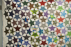 On my last week at the library, I asked Lexie if she could bring in her quilt so I could finally have a full photo of it. This is Star Stories, three years later, after use and love.  For the archive page about the quilt, see domesticat.net/quilts/star-stories  For an excellent full write-up of what this quilt was, and why the fabrics had meaning, see domesticat.net/2009/10/quilt-festival-story-star-stories