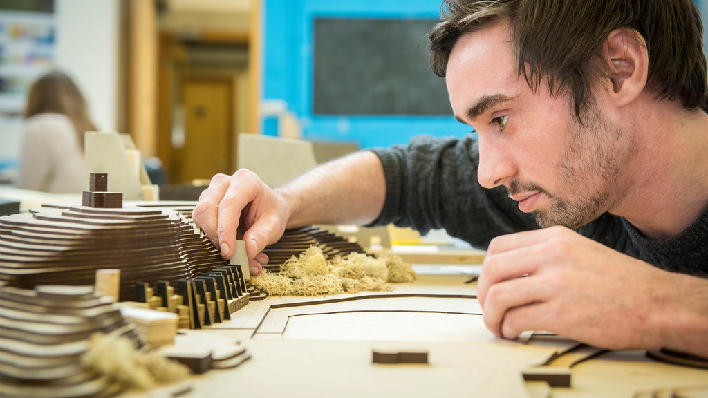 A student examines his wooden model.