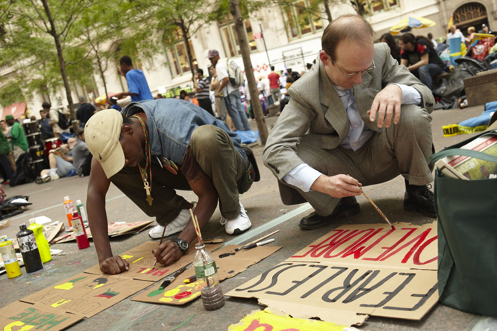 Men painting protest signs at the Occupy Wall Street Protests, New York City.