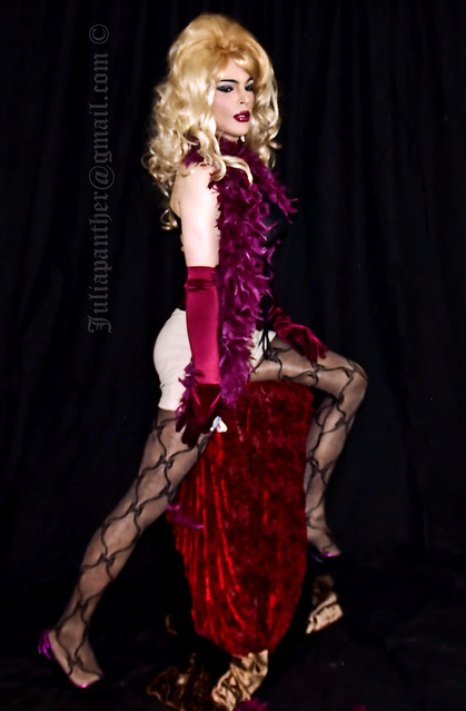 Legs in lace hosiery and heels with pink feather boa