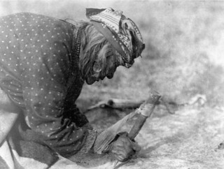 Blackfoot woman fleshing a hide using a long bone with a bevelled scraping edge, Alberta / Femme pied-noir grattant une peau au moyen d'un long os au bout en biseau (Alberta)