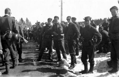 Norske, kapitulerte soldater ser bergjegere marsjere forbi
