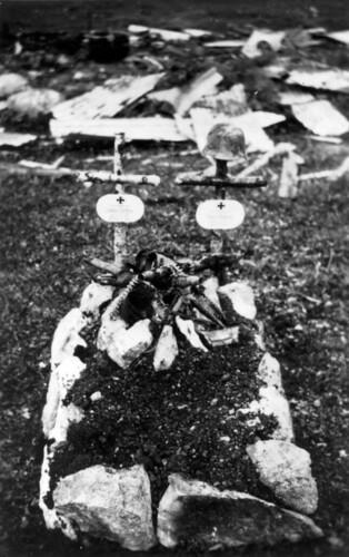 To tyske krigsgraver. Et maskingevær lagt på graven.