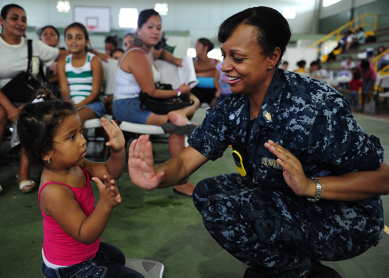 Iowa native/Sailor plays patty-cake with a child.