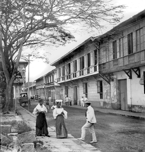 A prominent street in Intramuros, Manila, Philippines, late 19th or early 20th Century  This is probably General Luna street but it could be Cabildo Street