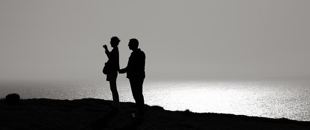 Young couple silhouetted against the sea