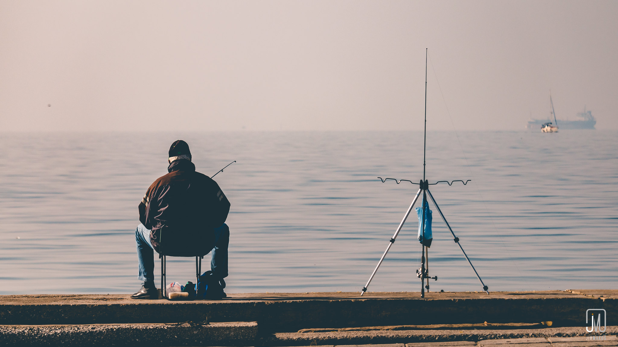Man sitting at the dock with his fishing rod on his hand and another one beside him