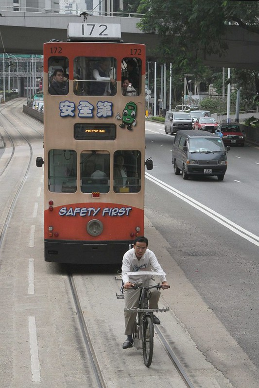 Man on a homebrew cargo bike rides on the tram tracks, with a 'Safety First' tram behind!