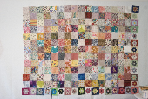 Jeff was independently busy this weekend, giving me time to sew. I have enough flower pieces to serve as a full border -- but not enough board space to put them up. As the piece contracts as the four-patches get sewn together, I'll have room to add them.