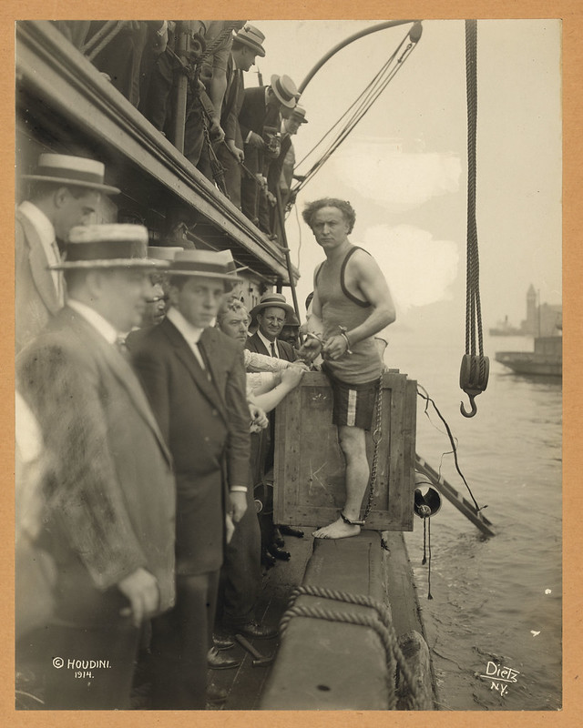 Houdini Straddles Crate Before Going Into Water, July 1914