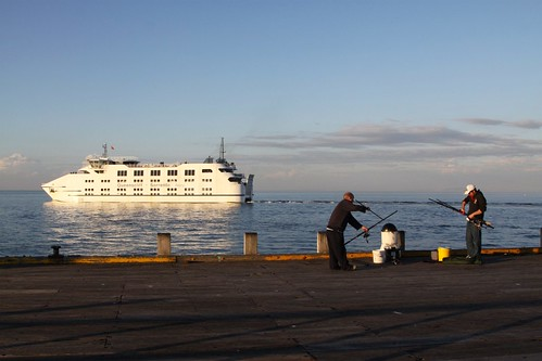 The car ferry passes fishermen packing up