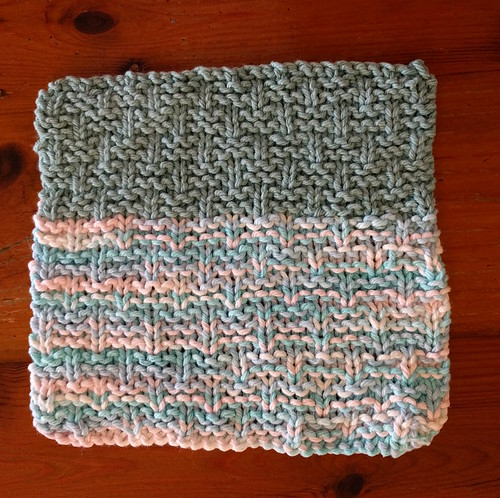 A knitted dishcloth in a basketweave pattern, part teal and part variegated blue white yarn.