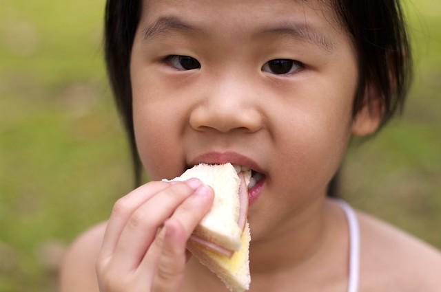 An Asian child eating a sandwich.