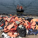 Migrants and refugees arrive by dinghy behind a huge pile of life vests after crossing from Turkey