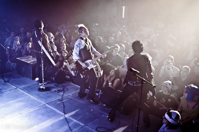 hind view of band The Slants performing for crowd