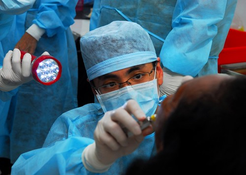 Singapore Military Force Capt. (Dr.) Desmond Ng performs a tooth extraction during a dental civic   by U.S. Embassy Jakarta, Indonesia