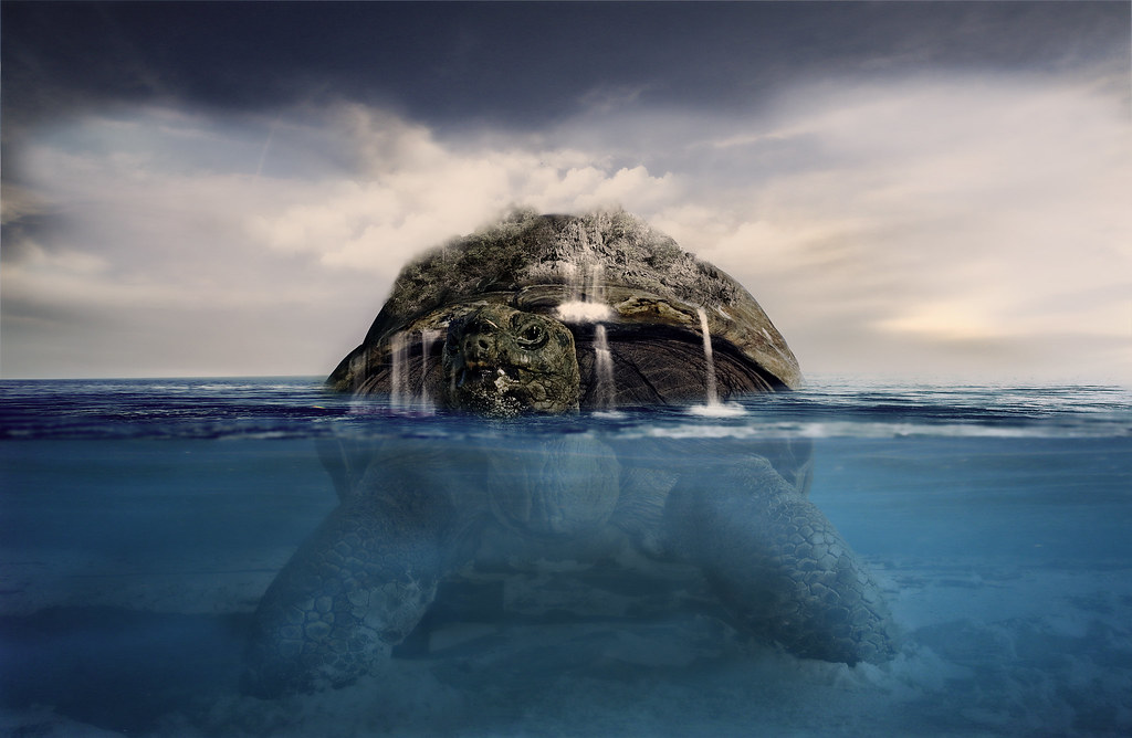Image of a large turtle in the ocean with land on its back.
