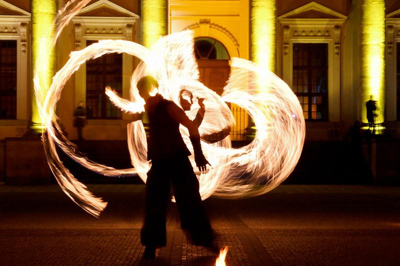 Sihuette eines Poi Spieler vor Kreisen aus Feuer