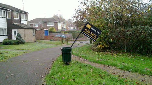 Slightly amusing photo of for-sale sign in a bin