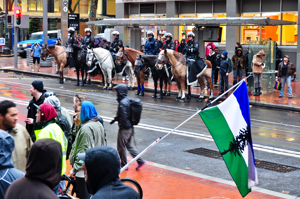 Mounted police watch protesters with Cascadia secessionist