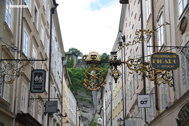 Liikkeiden kylttejä kauniiden rakennusten edustalla Salzburgin keskustassa