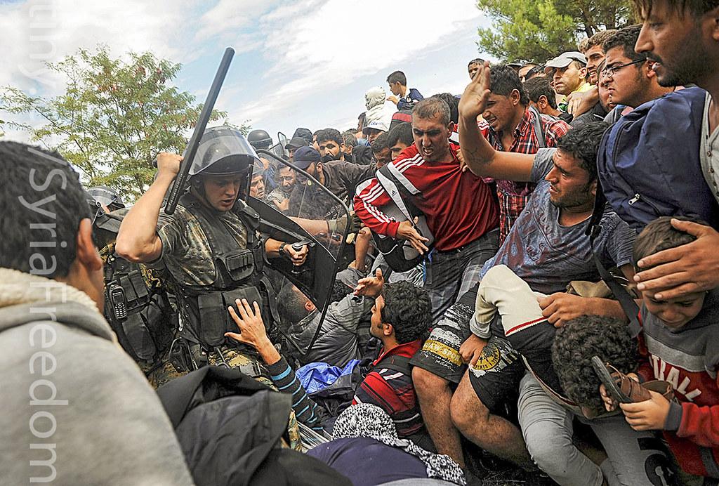 A Macedonian police officer raises his baton toward migrants.