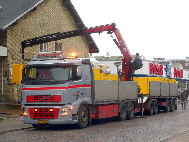 driver sits on crane over Volvo FH16 VY90327 unloading building materials